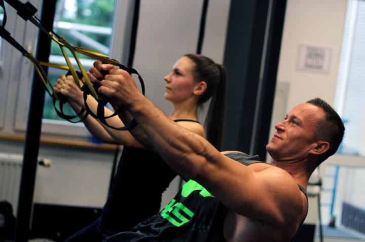 szkolenie trening w zawieszeniu, mężczyzna i kobieta ćwiczą z taśmami