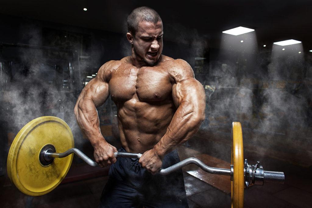 Atletyczny mężczyzna trenujący biceps ze sztangą