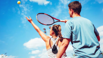 Instruktor tenisa zimnego i kobieta ćwicząca serw