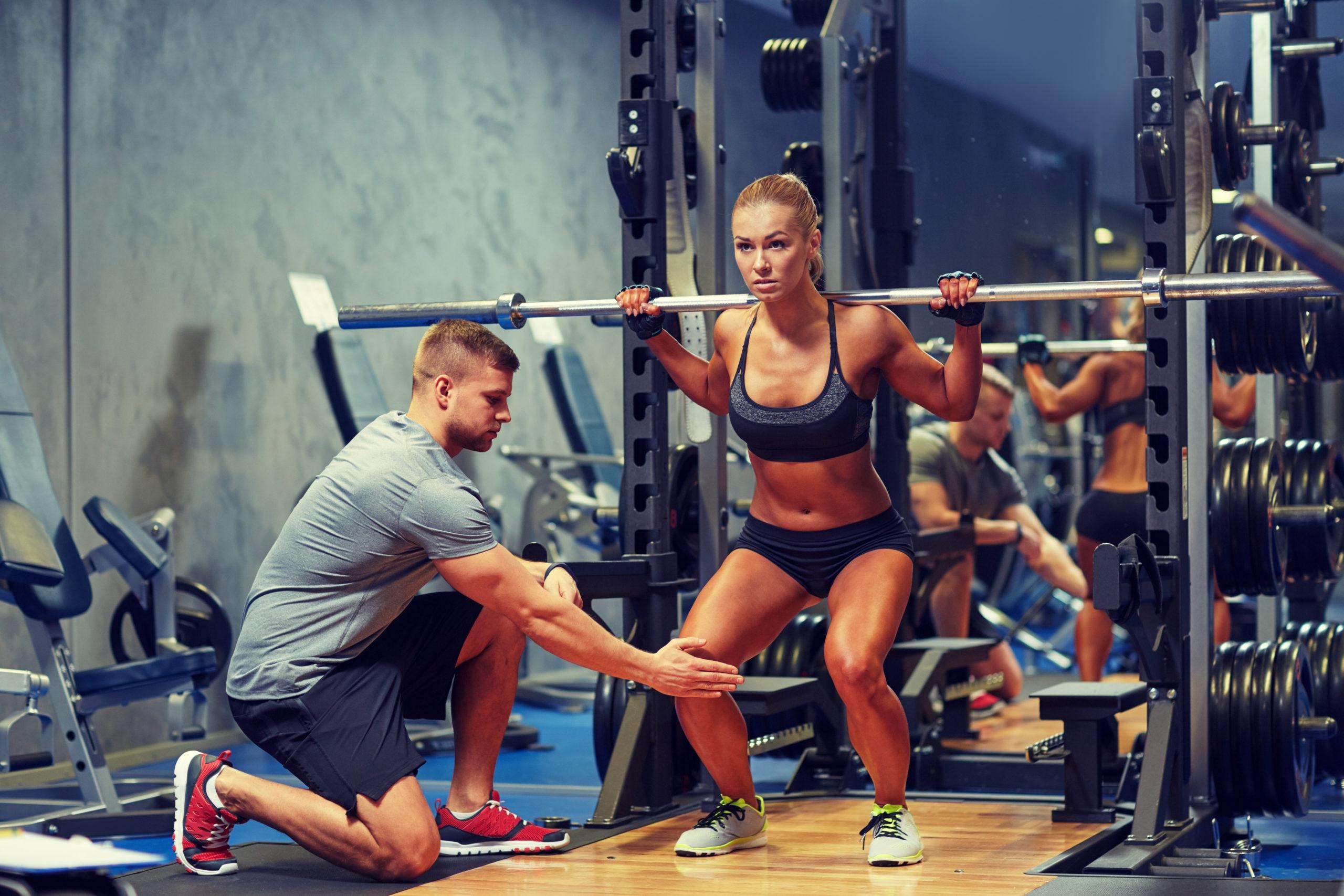 kobieta wykonująca przysiad ze sztangą; trener freelancer, trener na umowie, trener na etacie