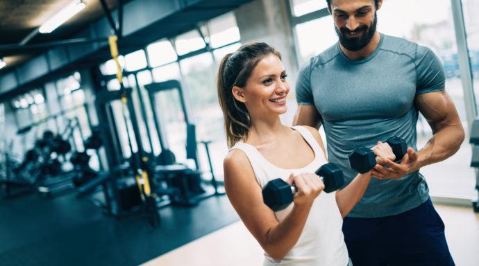 kobieta podnosi ciężarki, trener personalny; jak zostać trenerem personalnym