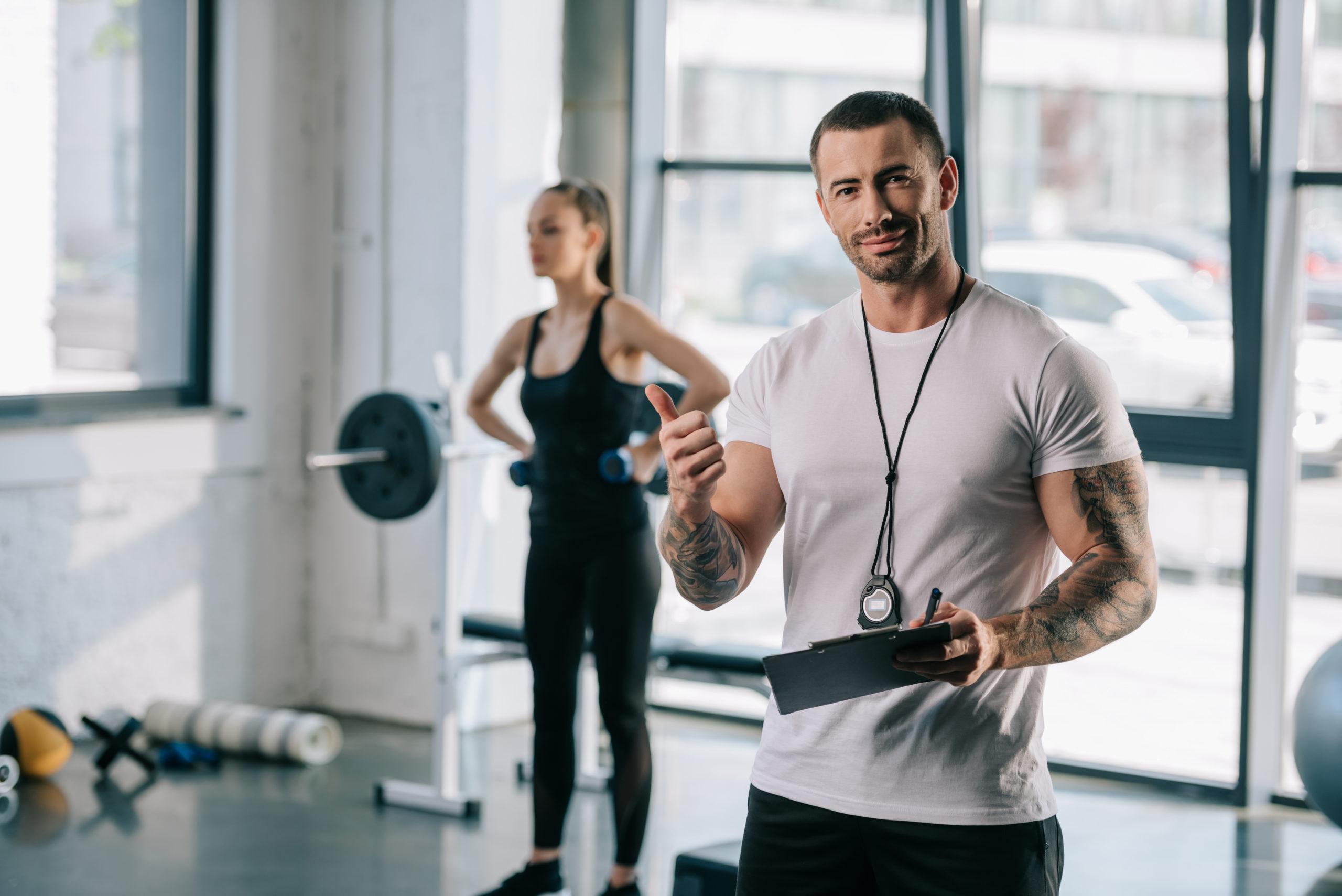 trener personalny i ćwicząca kobieta; jak wybrać kurs na trenera personalnego
