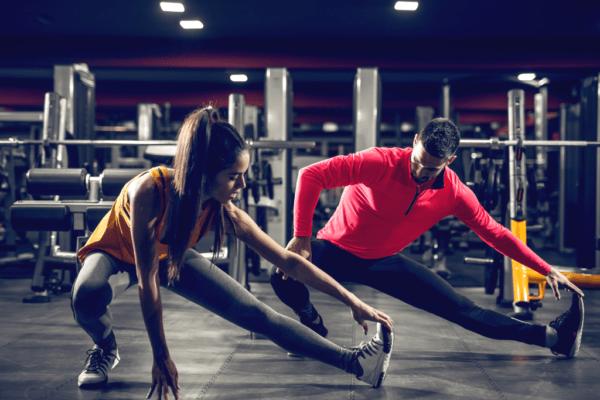 mężczyzna i kobieta rozciągający się na siłowni, indywidualny kurs trenera personalnego