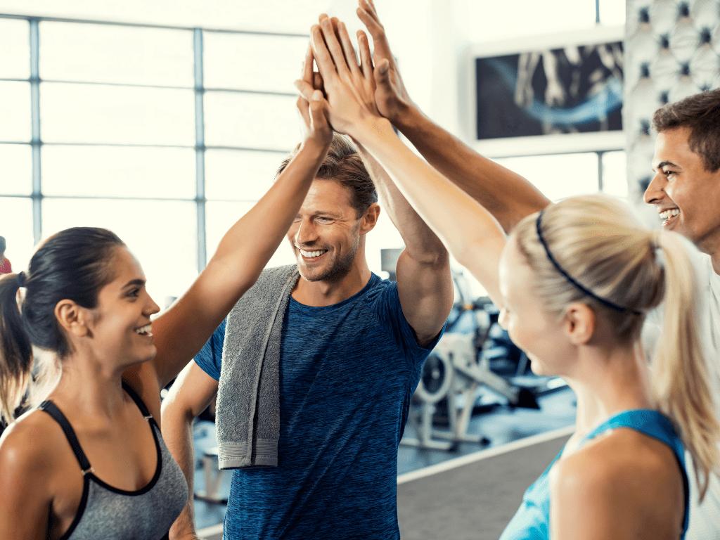 ludzie na siłowni przybijający sobie piątkę, kurs trenera personalnego