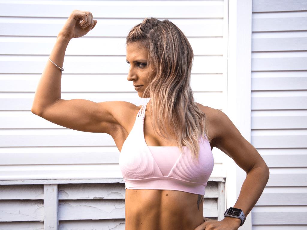 kobieta napinająca biceps; treningi personalne