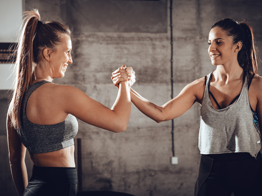 zadowolone kobiety na siłowni podające sobie ręce; cross training
