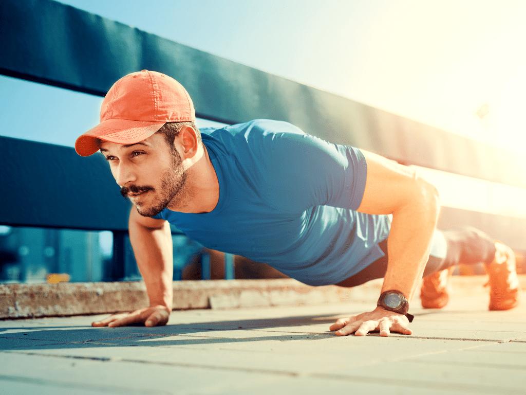 mężczyzna robiący pompkę; jak trenować podczas upałów
