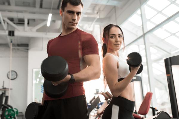 kobieta i mężczyzna z hantelkami; motywacja do treningu