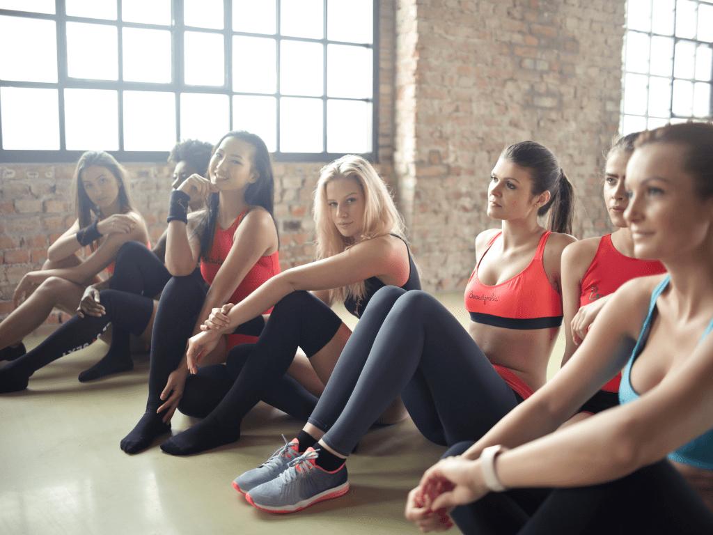 uczestnicy zajęć fitness siedzą na podłodze; kurs na instruktora fitness