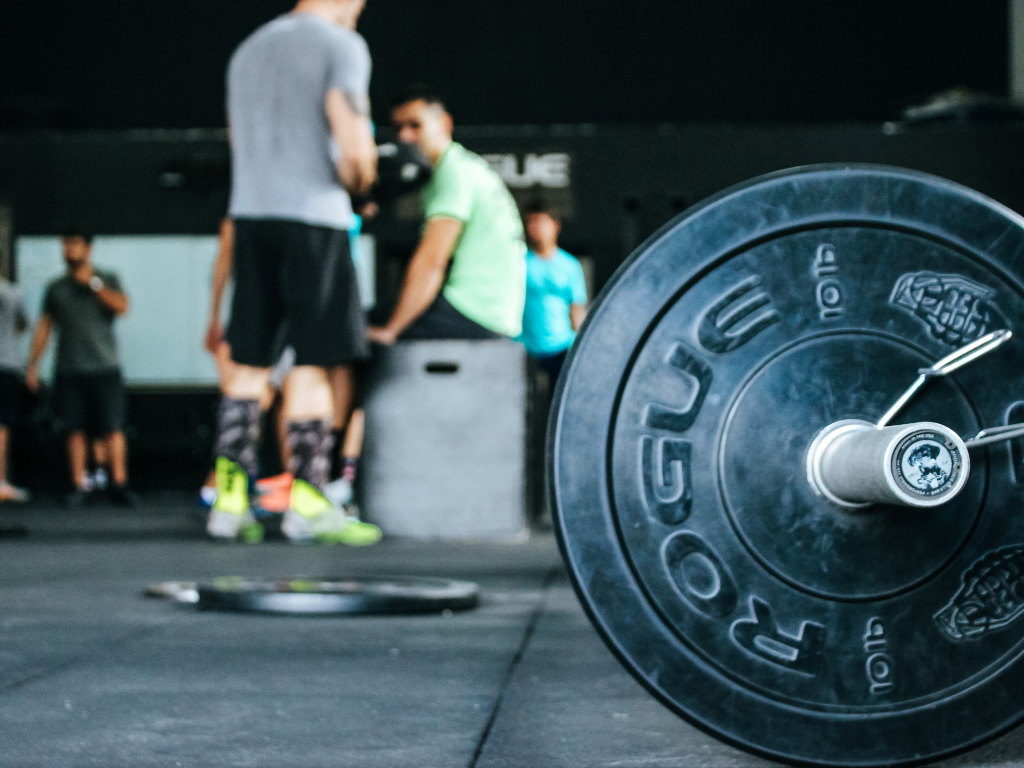 sztanga i ludzie w tle na siłowni; pakiet trener personalny pro silver