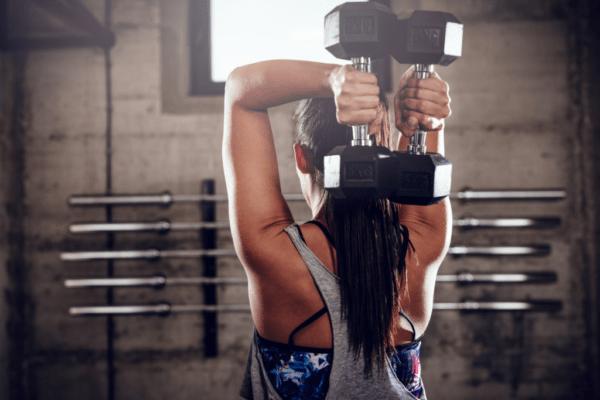 kobieta trzymająca ciężarki za plecami; kurs na trenera personalnego