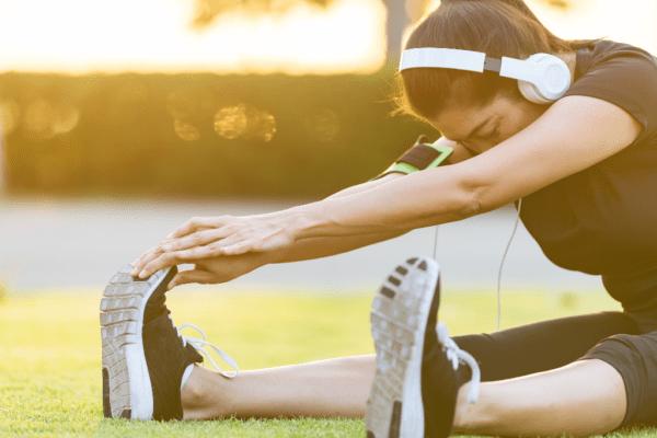 kobieta rozciągająca się na trawie; dlaczego warto się rozciągać