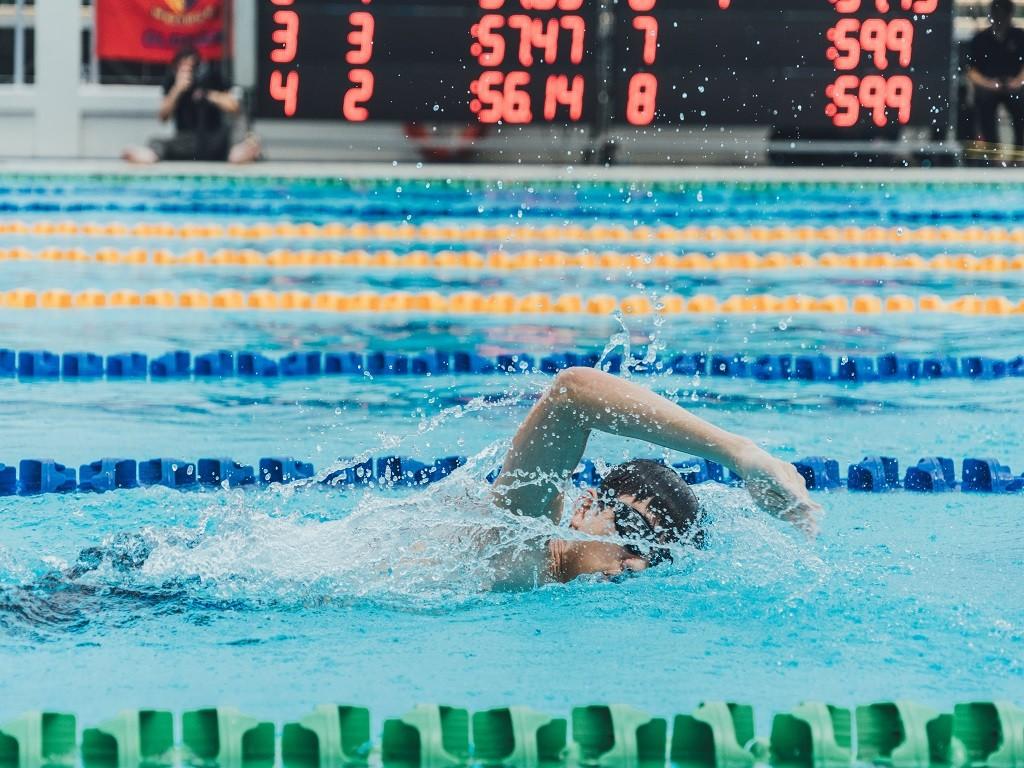 mężczyzna pływający w basenie, zalety pływania, dlaczego warto pływać
