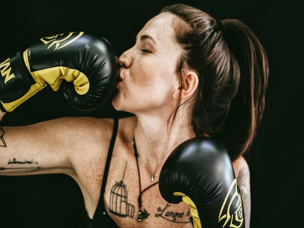 kobieta całująca rękawicę bokserską, boks, sport walki, odważ się na boks