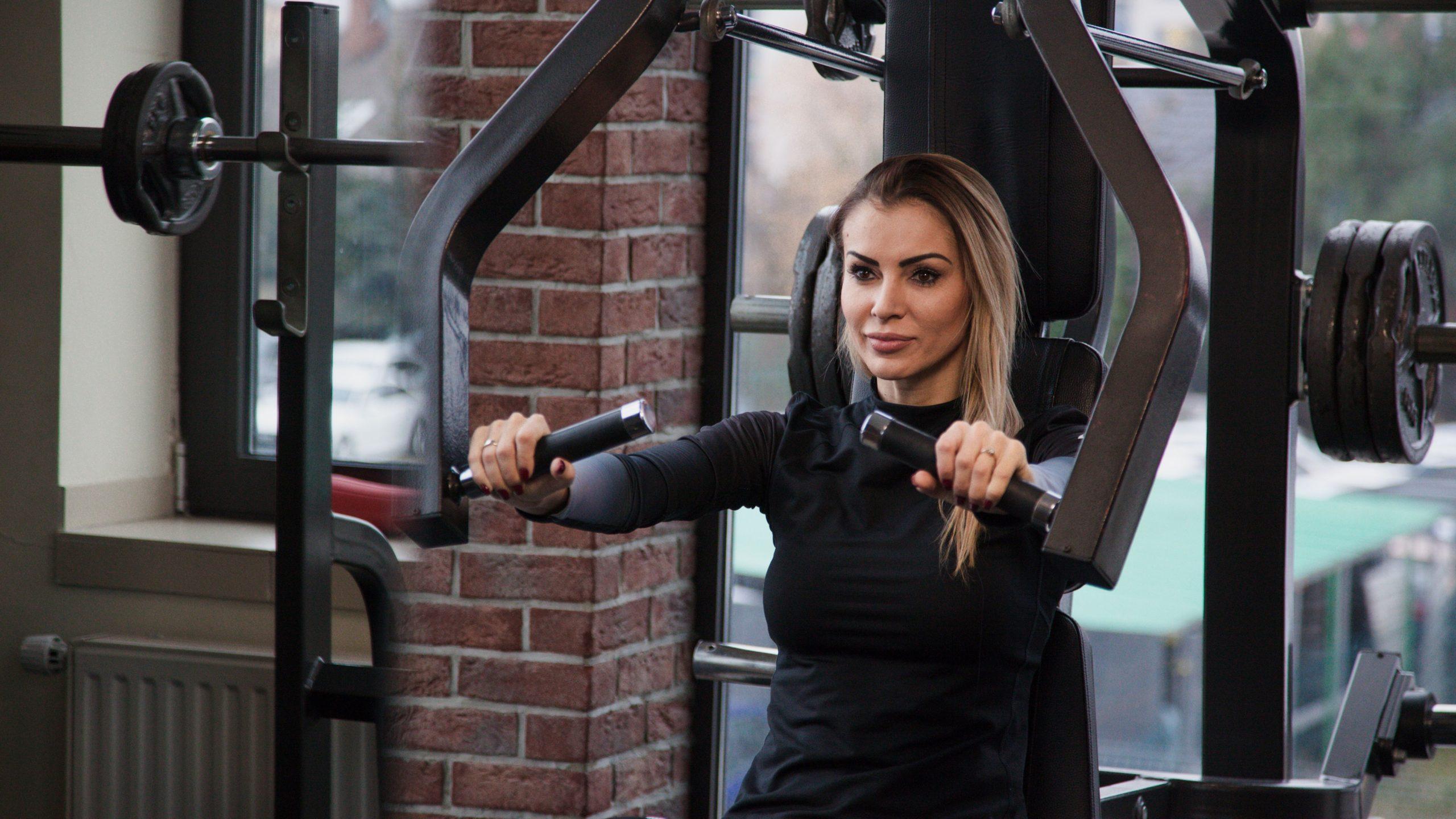 kobieta ćwicząca na sprzęcie na siłowni