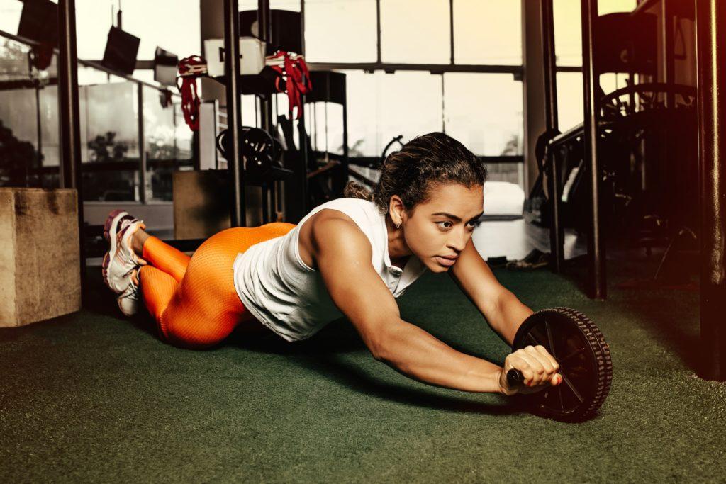 kobieta robi ćwiczenie z krążkiem (kursy trenera personalnego, ile trwa kurs na trenera personalnego)