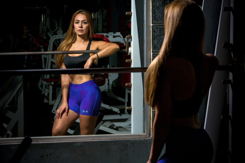 wysportowana kobieta przegląda się w lustrze (kursy trenera personalnego, ile trwa kurs na trenera personalnego)